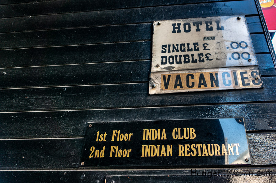 Signs showing India Club, restaurant and hotel vacancies in the same building.