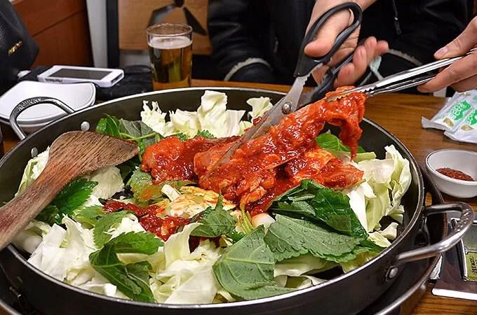 でっかい鍋に鶏肉がどーんと真ん中にのっていますね! そして野菜たっぷり!中にはさつまいも、キャベツ、ごまの葉やお餅など具だくさん♪