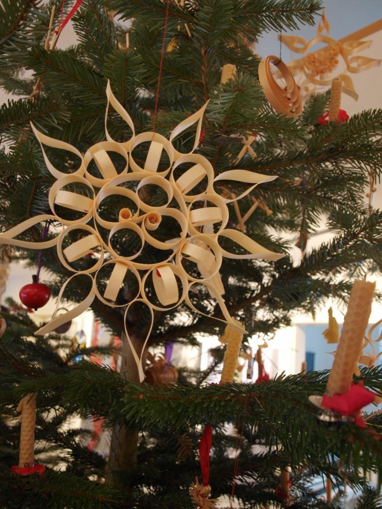 Weihnachtsbaum geschmückt mit Bienenwachskerzen, Strohsternen und Schmuck aus Holzspan