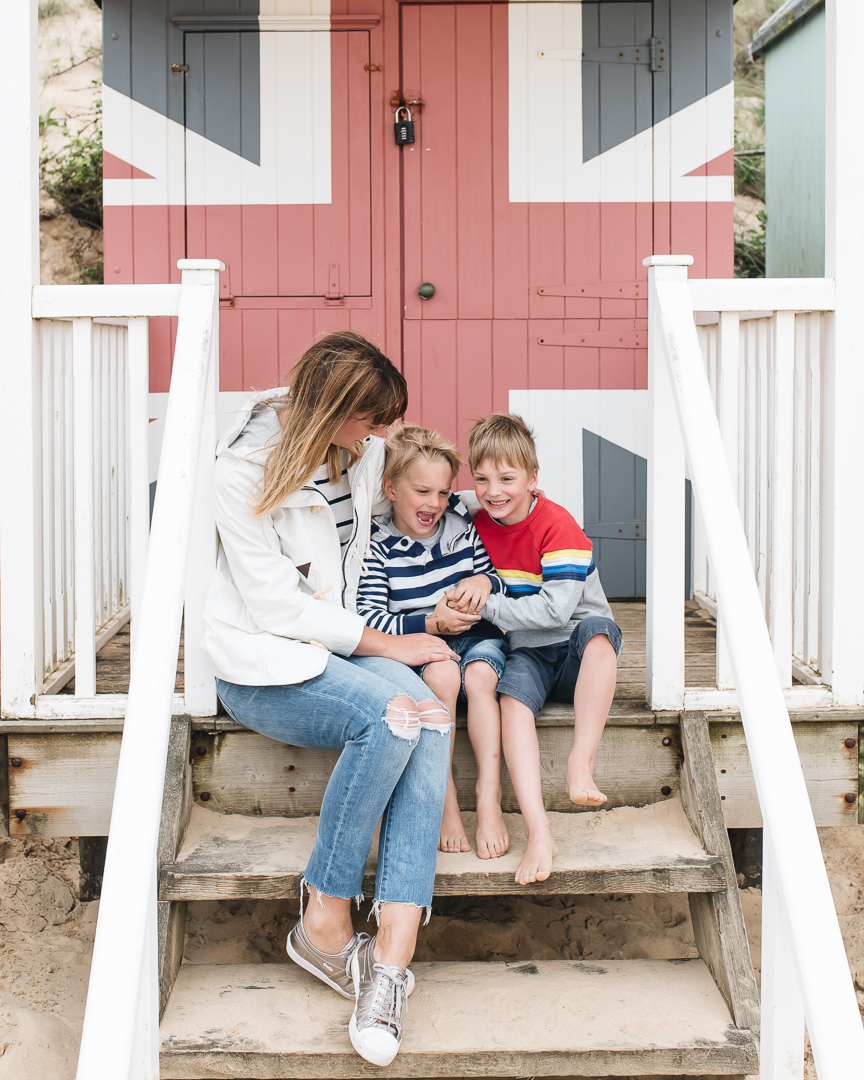 family by a beach hut at wells next the sea