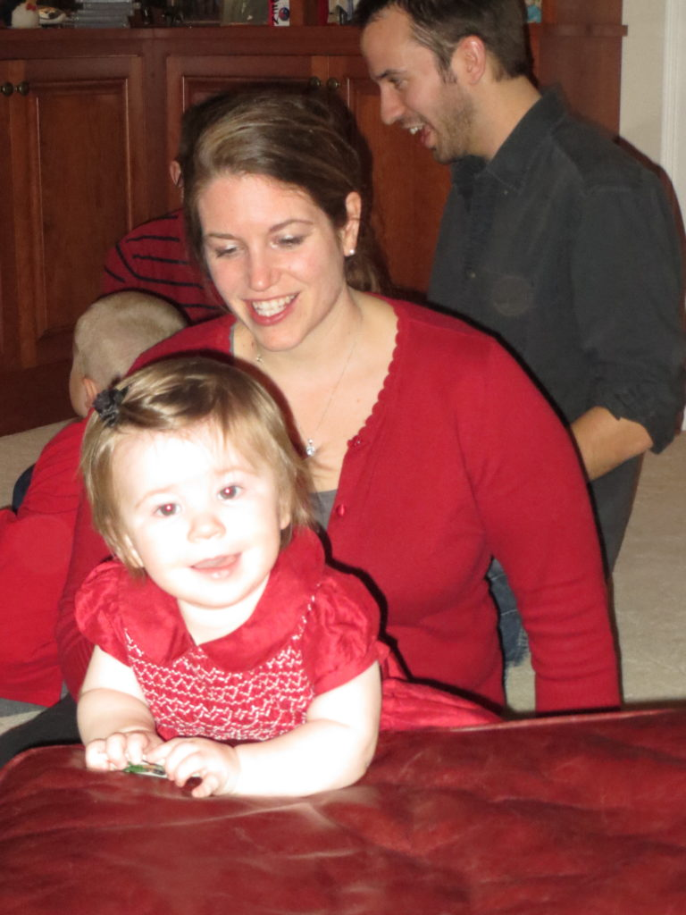 Eliza joyfully clutches an Uncle Wiggily game piece while Mom Becca looks on