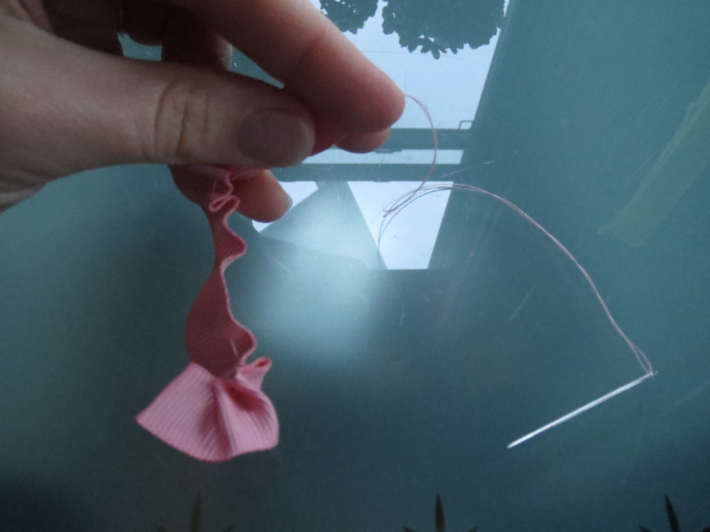 pulling the ribbon down the thread