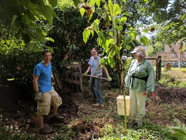 photo: three people gathered around compost pile