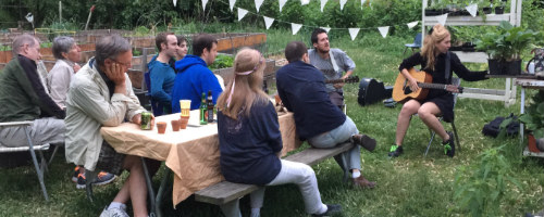 photo: people seated at picnic table listening to musicians