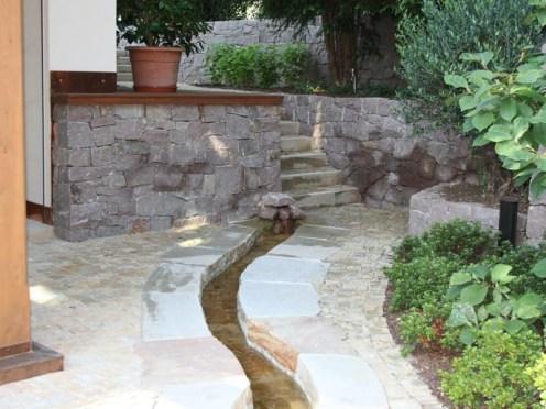 Wie ein natürlicher Bach, der aus einem Fels entspringt, wirkt dieser Bachlauf, neben dem ein weiterer Weg des Gartens verläuft.