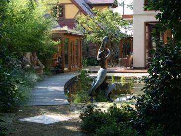 Die Nymphe, die auf den Namen Marianne getauft wurde, erhebt sich über dem Gartenteich. Links im Hintergrund noch ein kleiner Blick auf die Orangerie, wo die frostempfindlichen Kübelpflanzen im Winter Schutz finden.