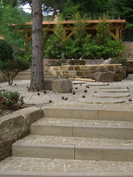 Die Sandsteintreppe mit Sandsteinpflaster führt in den asiatischen Gartenteil, der sich unter hohen, alten Kiefern befindet.