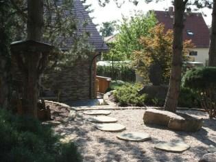 Unter den prächtigen, erhaltenen Kiefern führt ein aus Sandsteinplatten gestalteter Weg über die bewusst spartanisch gestaltete Kiesfläche des asiatische Gartenteils.