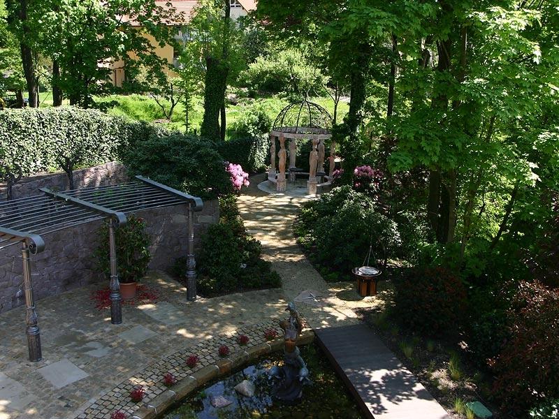 In einem solchen Gartenpark darf natürlich auch ein Teich nicht fehlen. Neben dem Teich nimmt eine sehr schöne Pergola die halbrunde Form des Teiches wieder auf und bietet einen Sonnenschutz für die Liegeflächen.