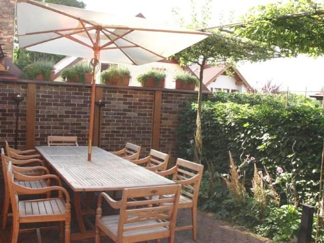 Der hausnahe Sitzplatz wird von einem Sonnenschirm in Kombination mit dem natürlichen Sonnenschutz von 2 Zieräpfelbäumen beschattet. Die Zieräpfel werden in Dachform vorgezogen, so dass sie bereits einen guten Sonnenschutz bieten, wenn Sie von uns geliefert werden.