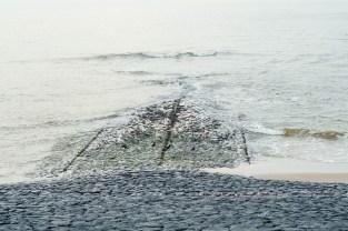 Een strekdam loopt onder water blij vloed.