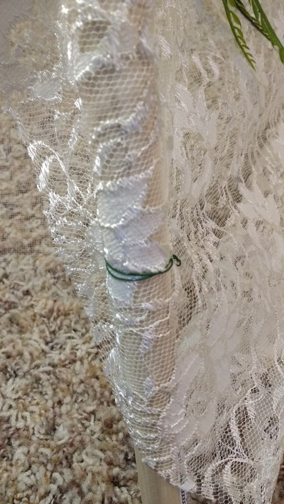 Unfold the lace and drape it over the rods. Center the lace on the rods, and cut two small holes to fit over the left and right side rods.
