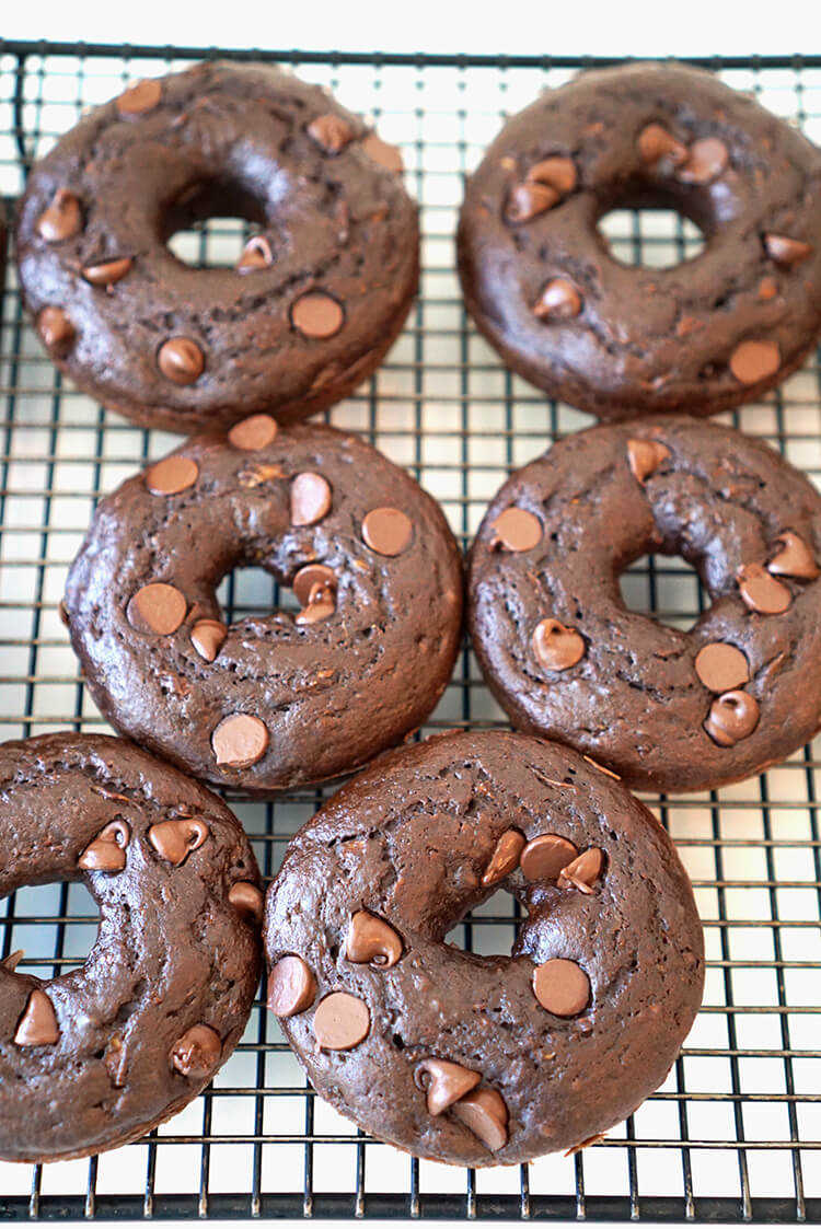 Healthy Chocolate Donuts - under 100 calories each - These moist and rich double chocolate cake donuts are under 100 calories each, and you'll never guess that they're packed full of zucchini and other better-for-you healthy ingredients!