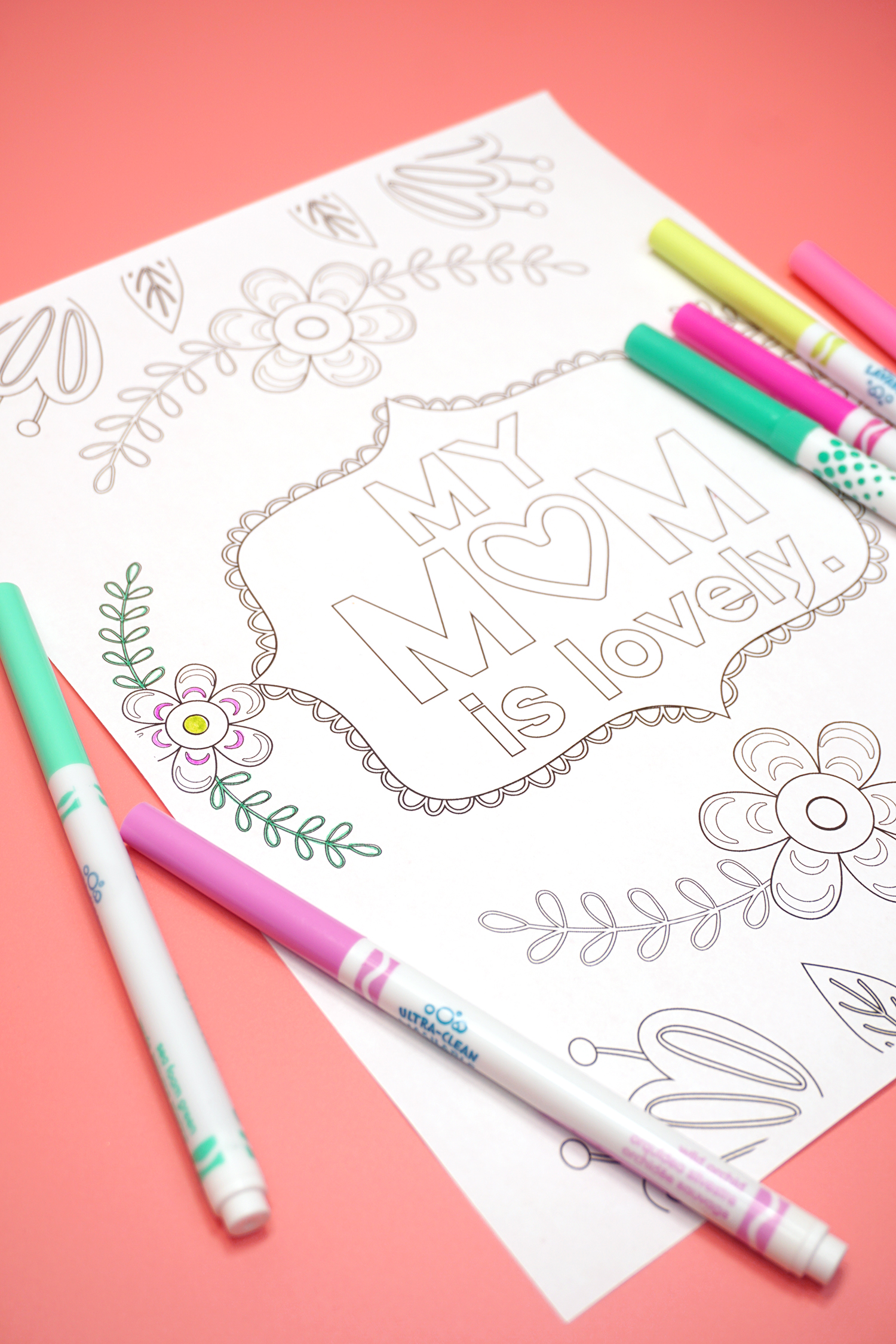 "Mother's Day Coloring Page ""My Mom is Lovely"" with markers on a coral background"