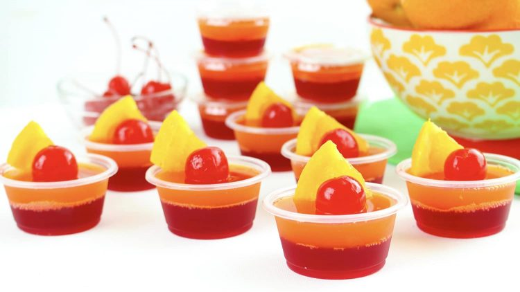Tequila Sunrise Jello shots with cherry and pineapple garnishes on a white table