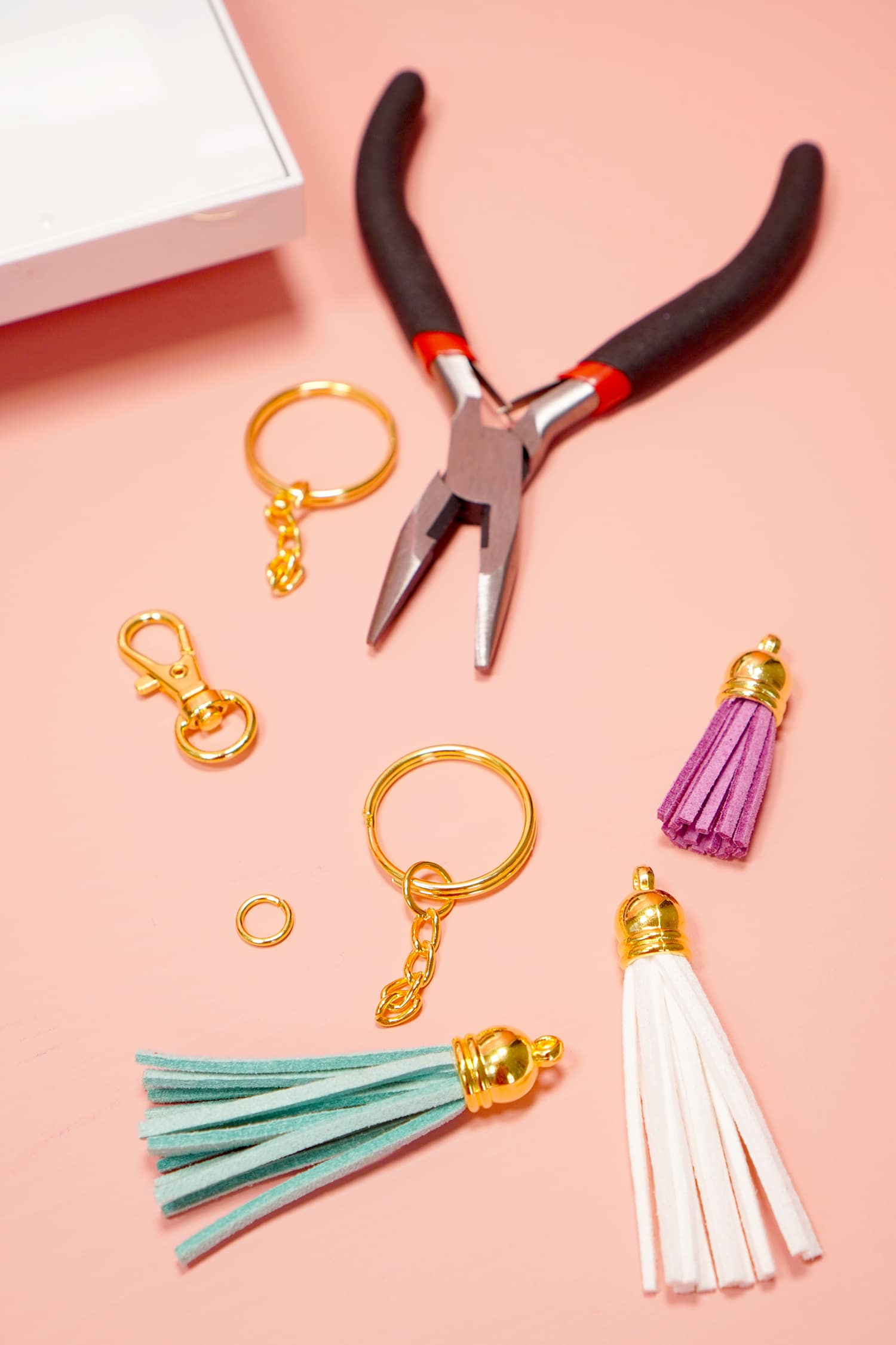 Jewelry and keychain making supplies on a peach background