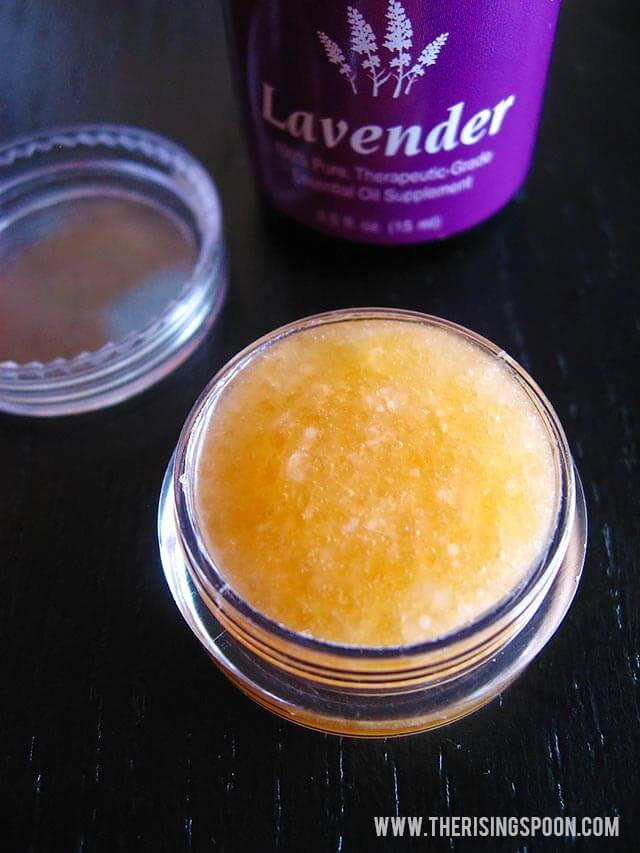 Small jar of honey lavender lip scrub with lavender essential oil bottle in background