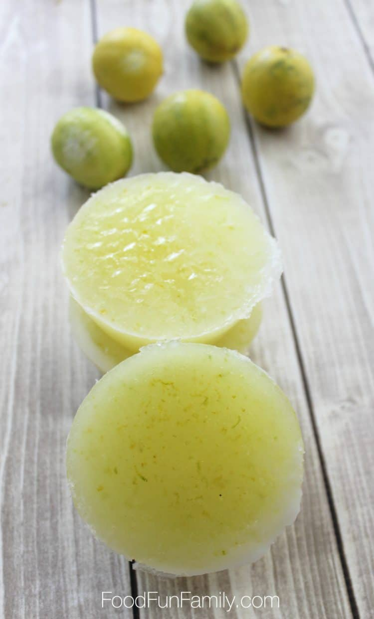 Lime and coconut sugar scrub bars on a wood background with limes