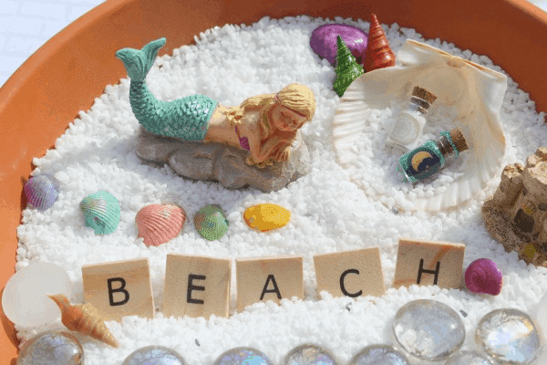 """mermaid fairy garden with the word \""""beach\"""""""