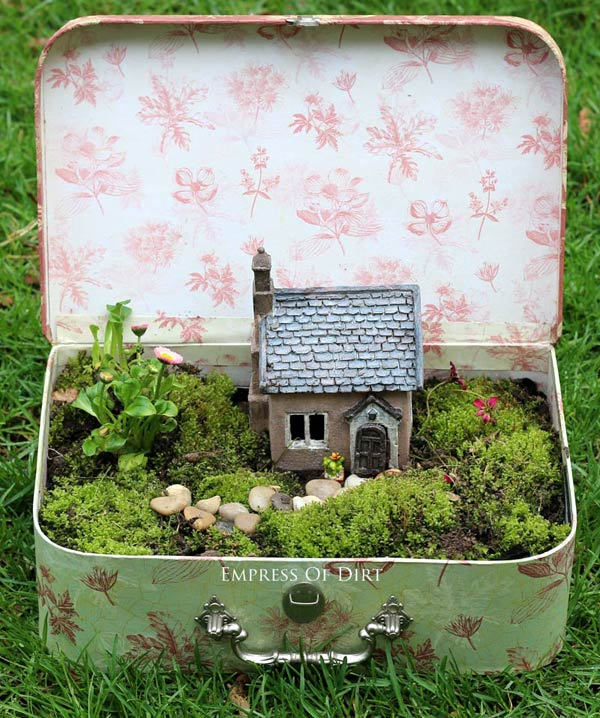Fairy garden in a recycled suitcase filled with greenery and a small fairy house