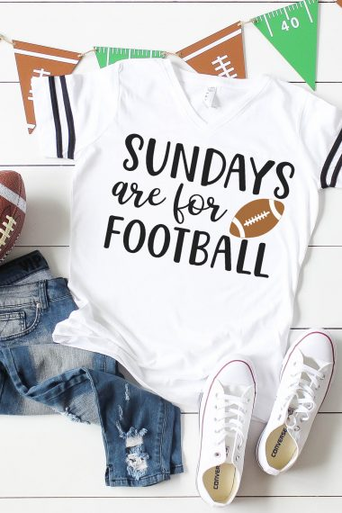 """Sundays are for Football"" Shirt on white wood background with football, jeans, white shoes, and football banner"
