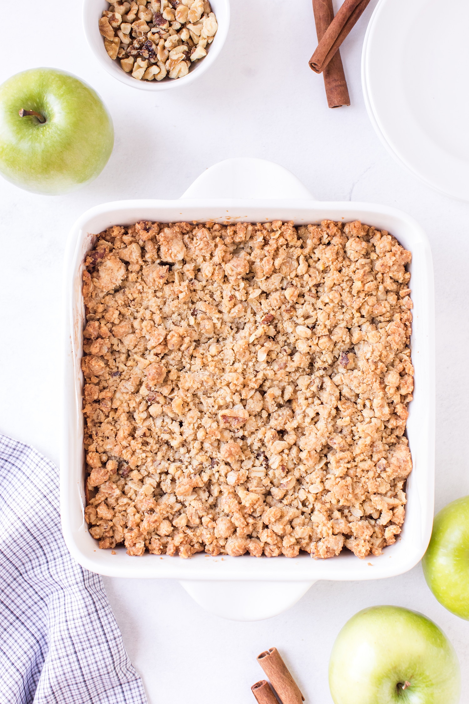 Apple pie bars with streusel topping in white backing dish with green apple on the side