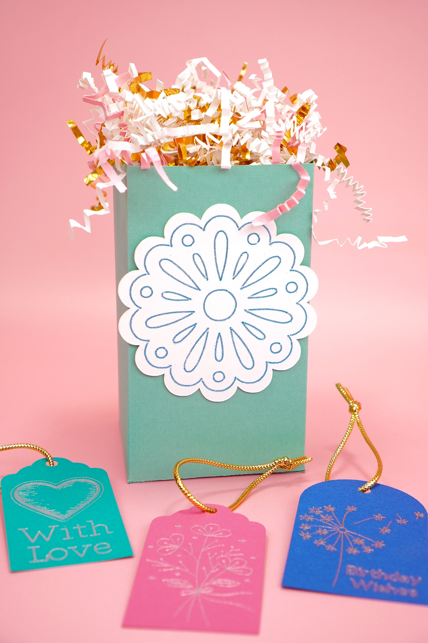 Mint green gift box with foil flower design and foil gift tags on pink background