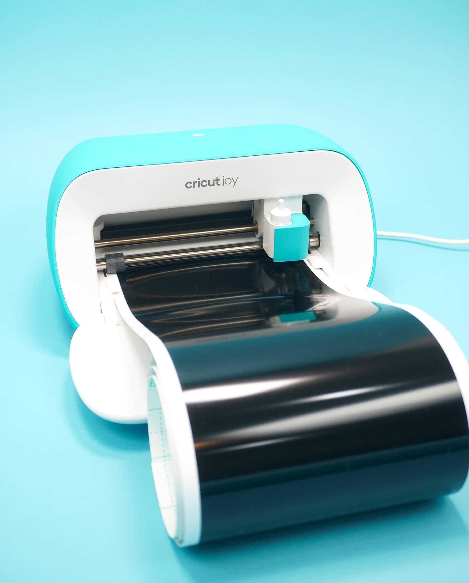Cricut Joy machine loaded with black Smart Vinyl on blue background