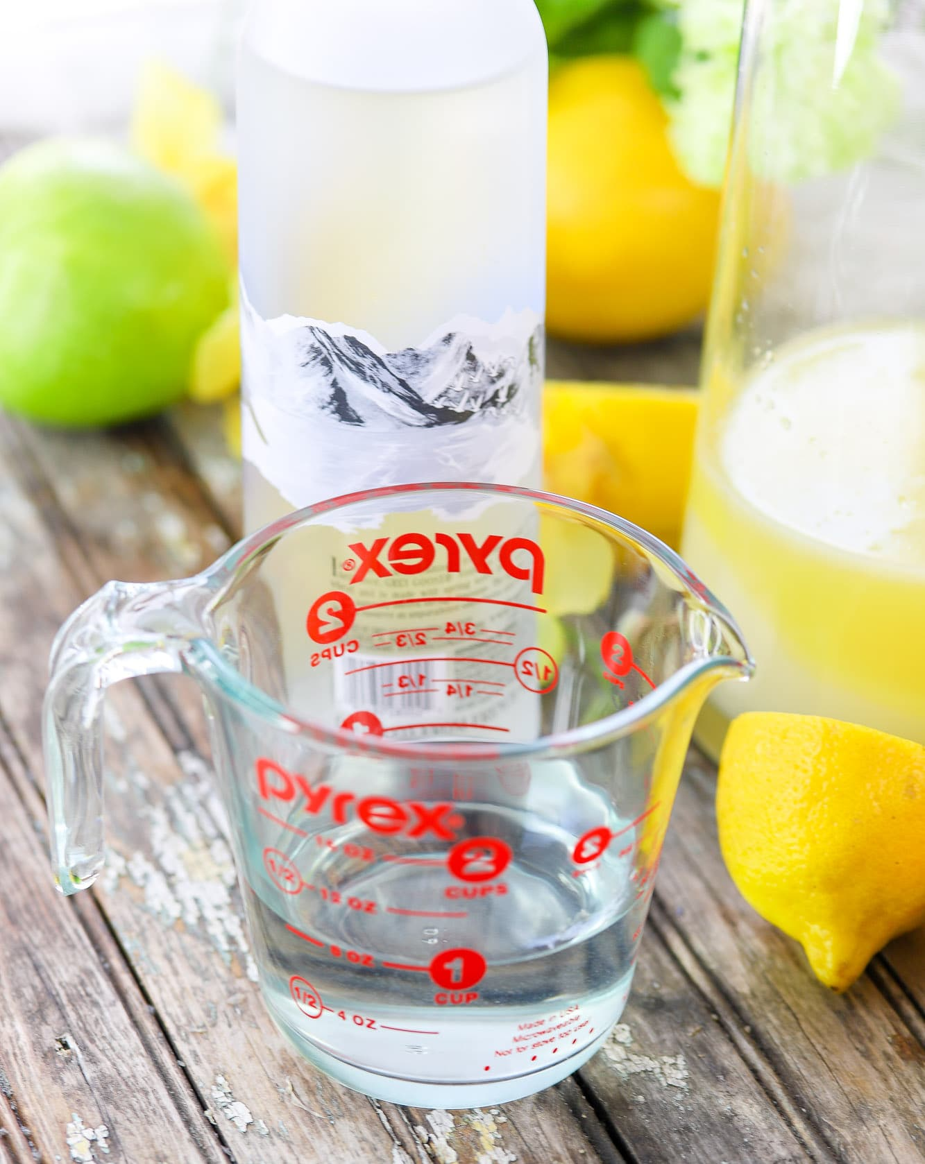 apple flavored vodka in a measuring cup with vodka bottle, lemons, and apples in background