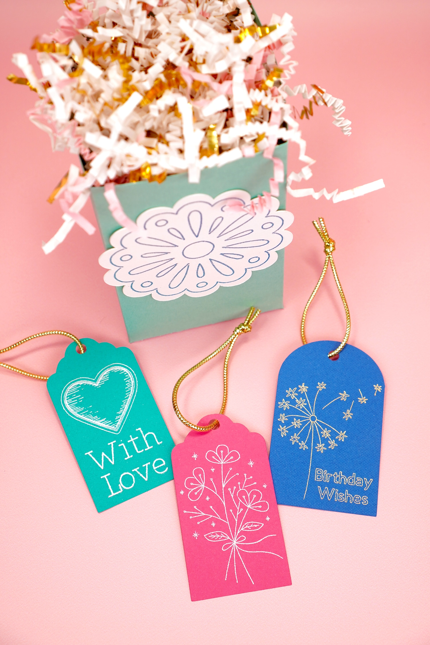 Colorful foil embellished gift tags and gift bag on coral background