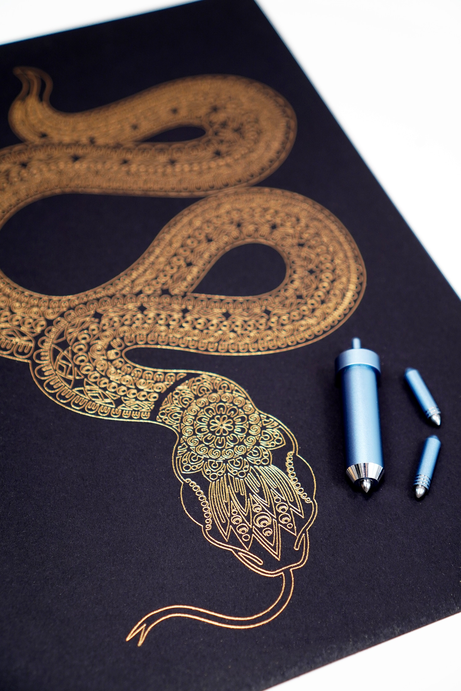Close up of gold foil art print detail - snake with mandala designs and Cricut Foil Transfer Tool on black