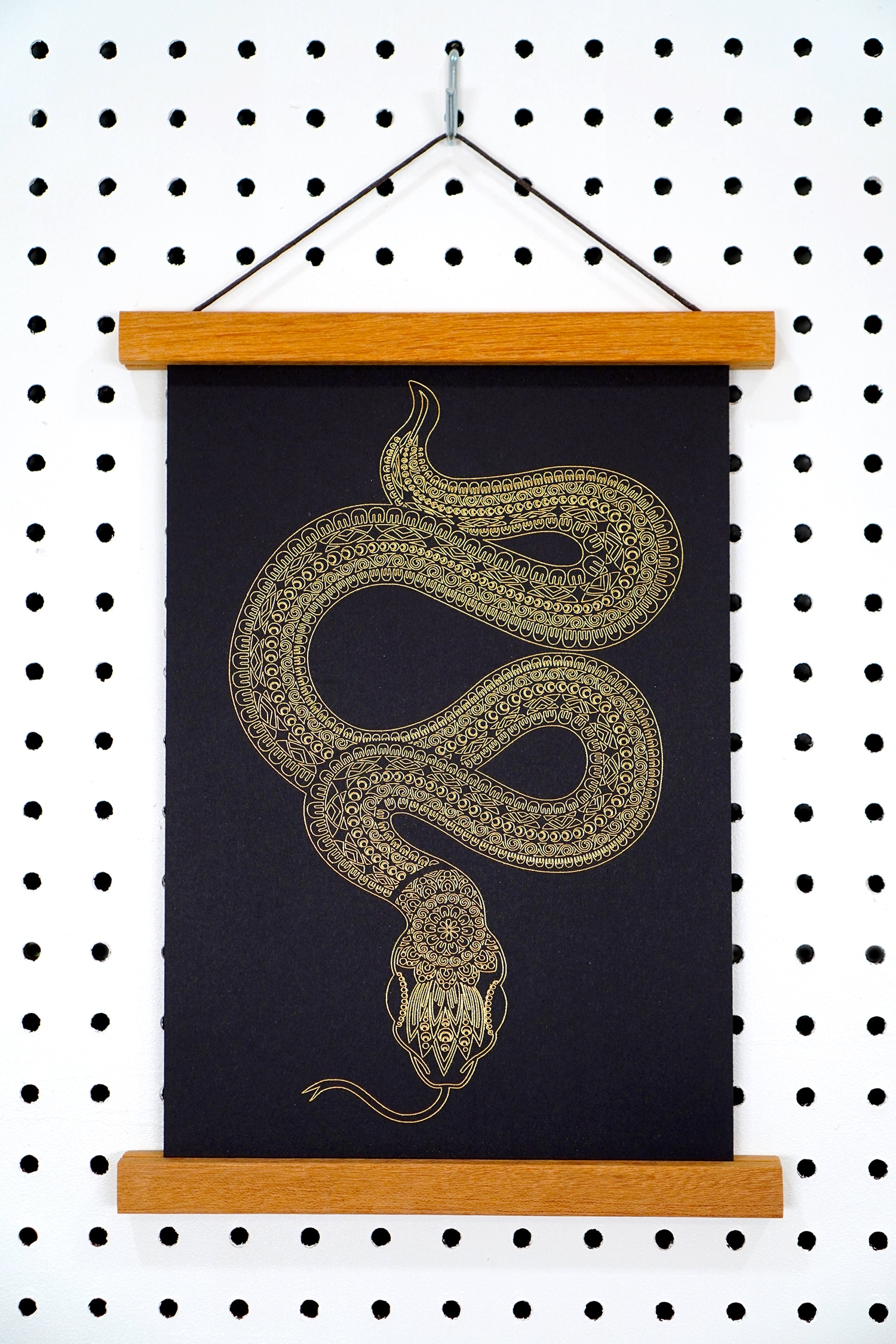 Gold foil art print of a snake with mandala design in wooden art hanger on pegboard