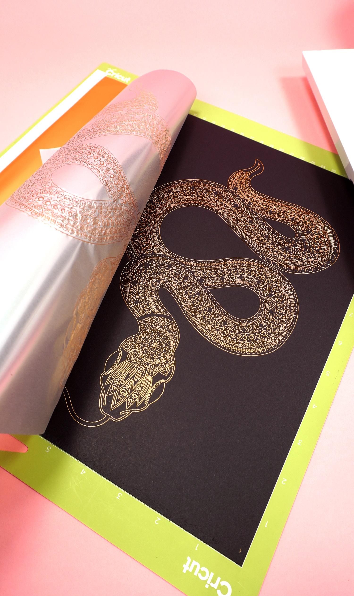 Peeling back gold foil transfer sheet to reveal gold foil art print of a snake