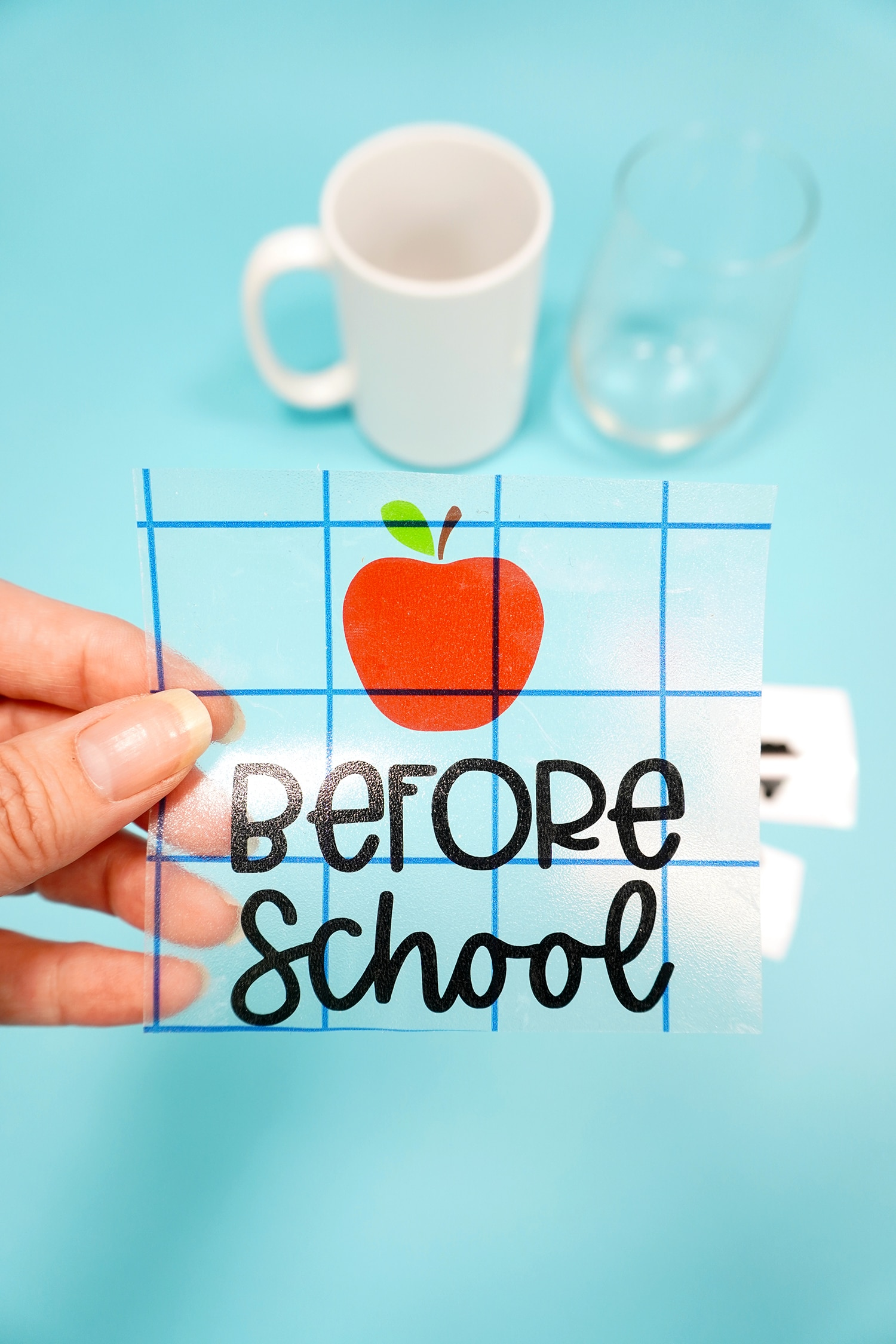 """Hand holding apple and """"before school"""" vinyl on transfer tape on blue backround"""