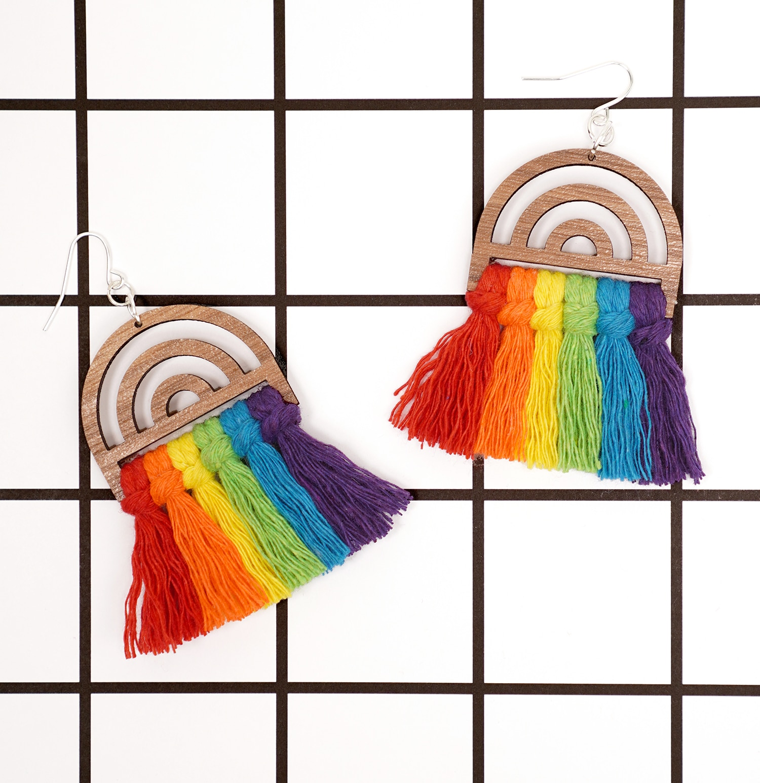 Rainbow macrame earrings on white background with bold black grid lines