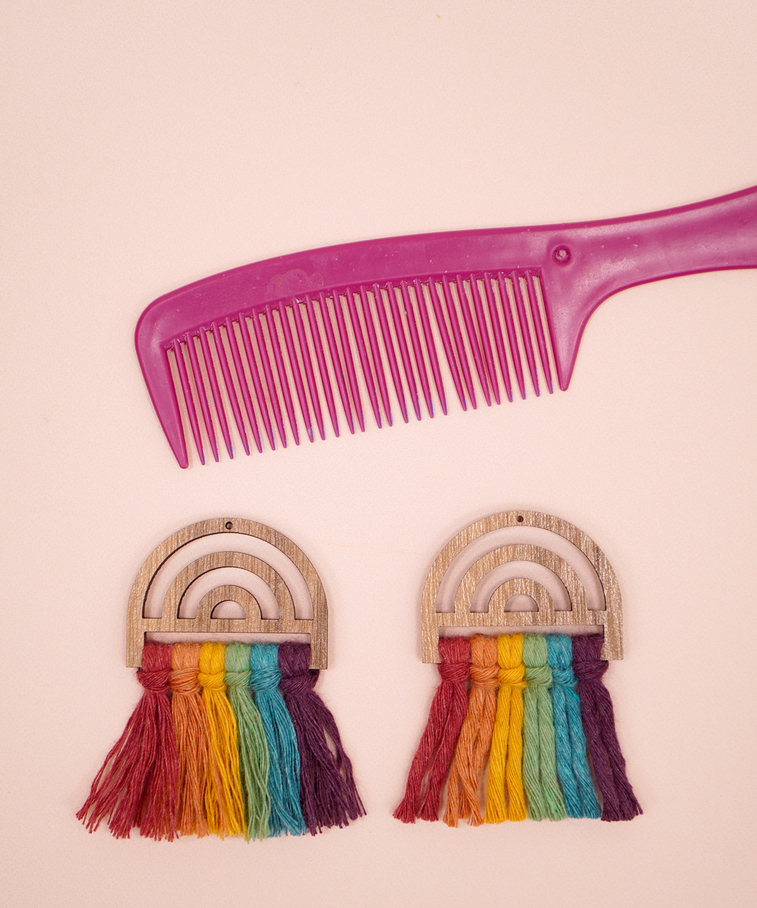 Comparing a brushed vs unbrushed rainbow wooden macrame earring with pink comb in background