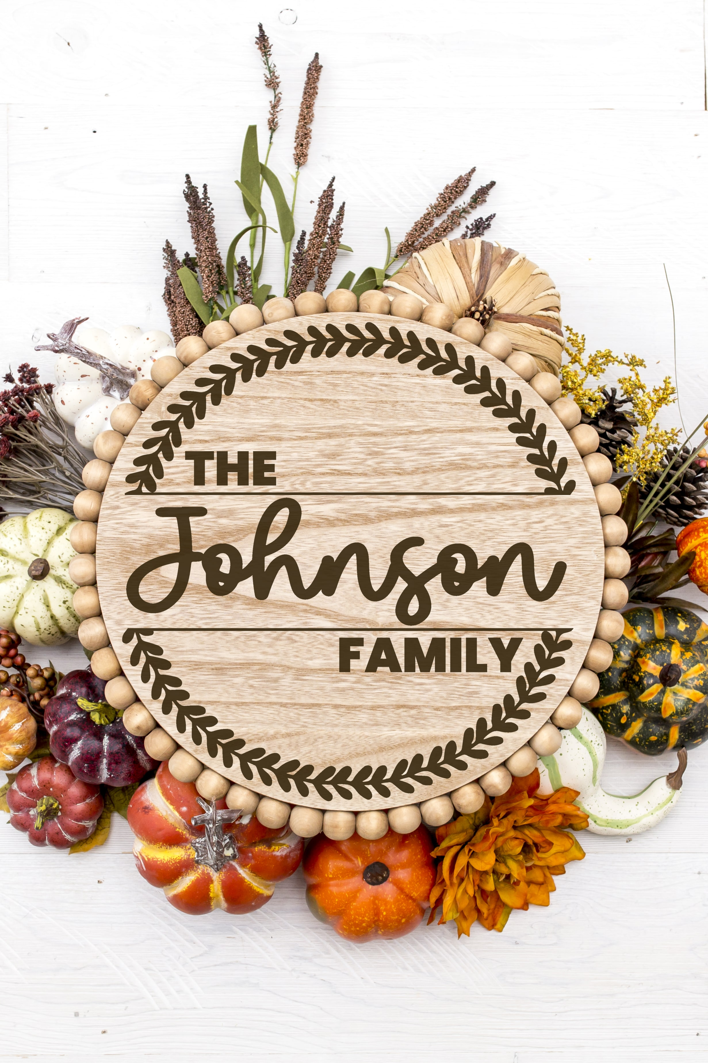 """Round wood wreath with """"The Johnson Family"""" design surrounded by fall pumpkins and foliage"""