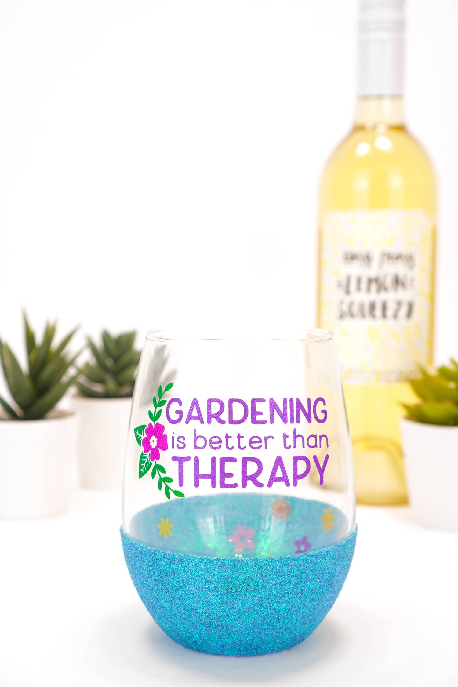 """""""Gardening is Better Than Therapy"""" stemless blue glitter wine glass on white background with plants"""