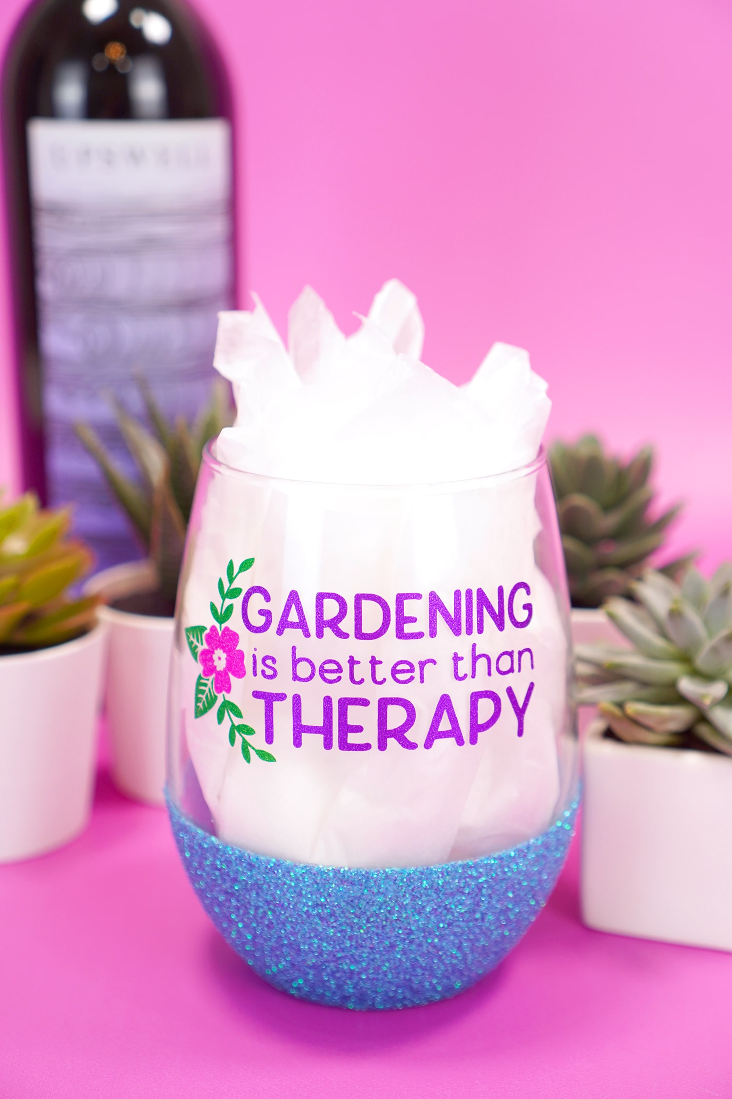 """""""Gardening is Better Than Therapy"""" stemless blue glitter wine glass on purple background with plants and wine bottle"""