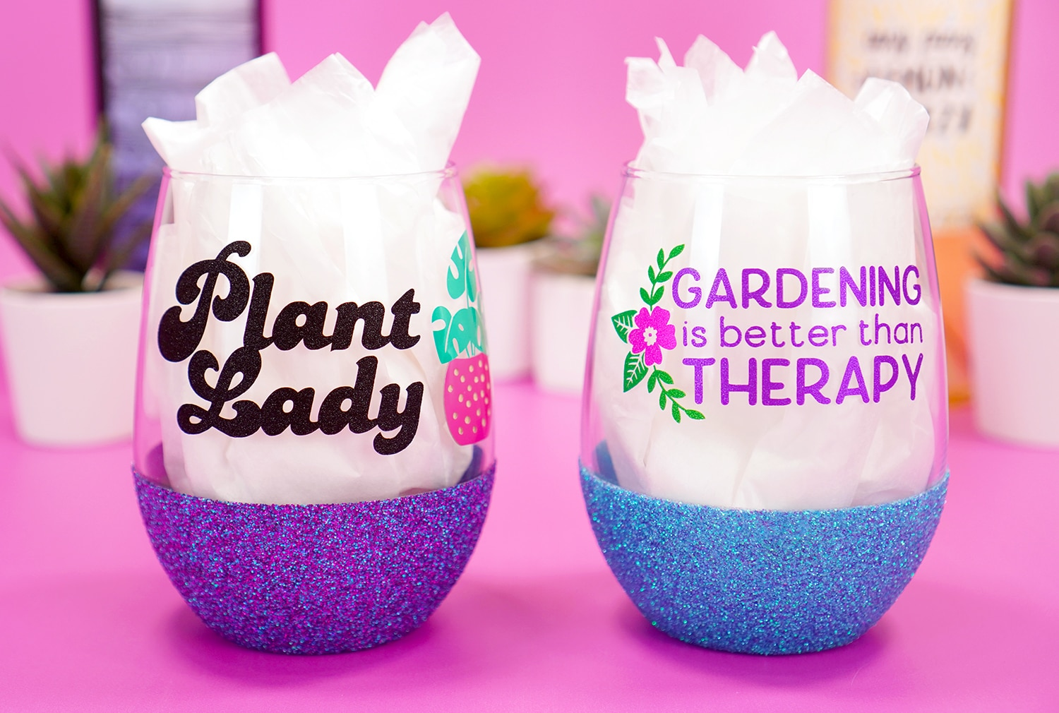 """""""Plant Lady"""" purple glitter wine glass and """"Gardening is Better Than Therapy"""" blue glittered wine glass on purple background with plants"""