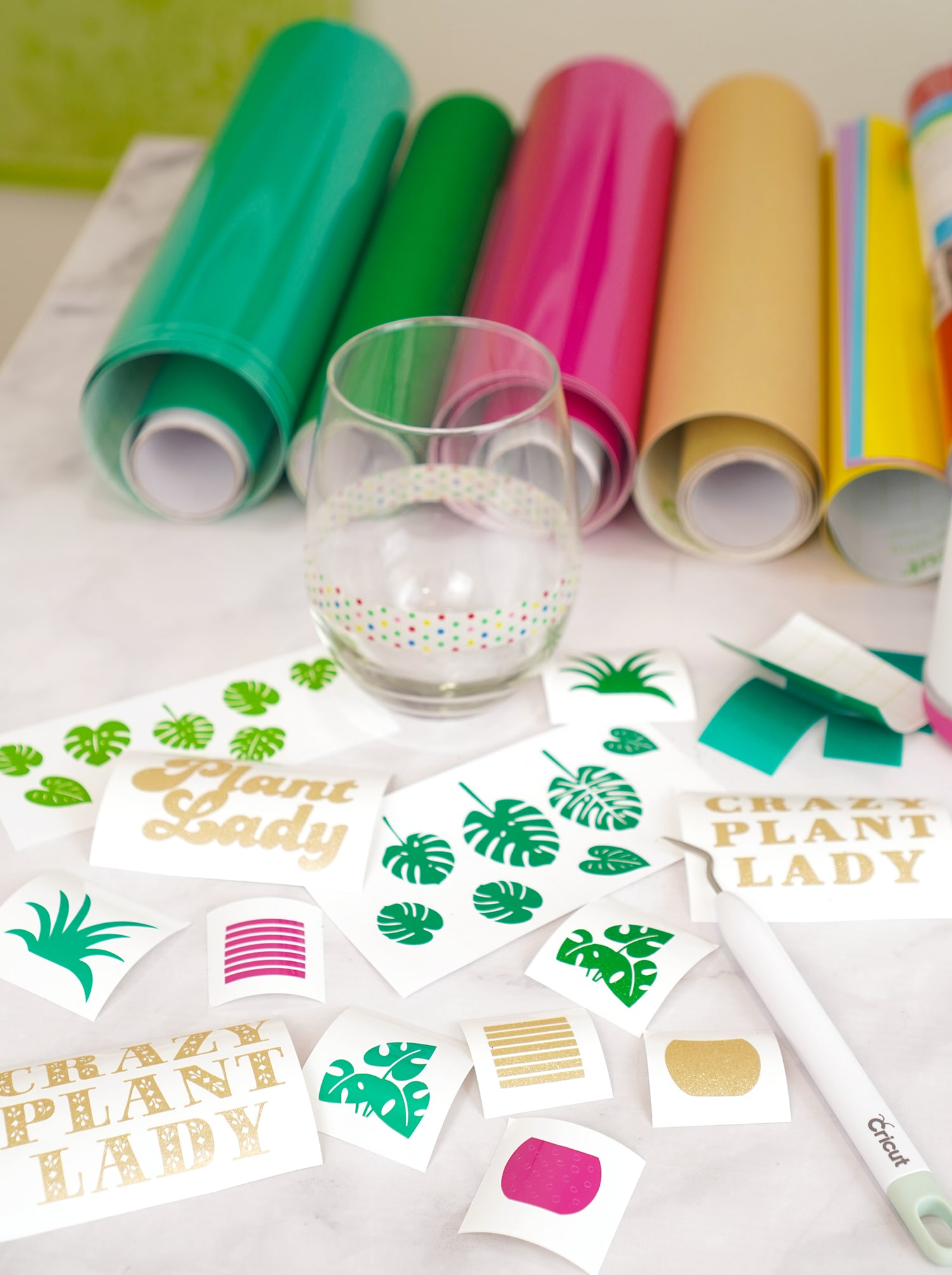 Weeded vinyl decals with weeding tool, vinyl rolls, and stemless wine glass