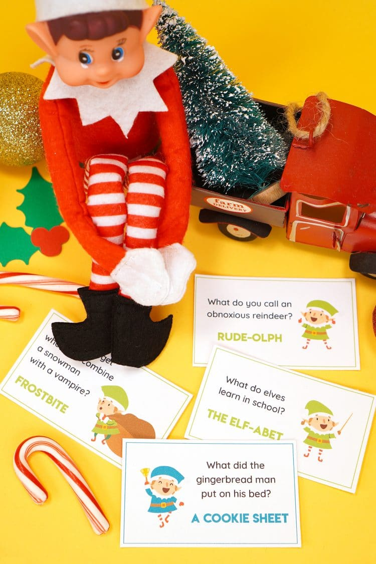 Elf doll on a yellow background with printed Elf on the Shelf joke cards scattered around him and candy canes and Christmas decorations in the background.