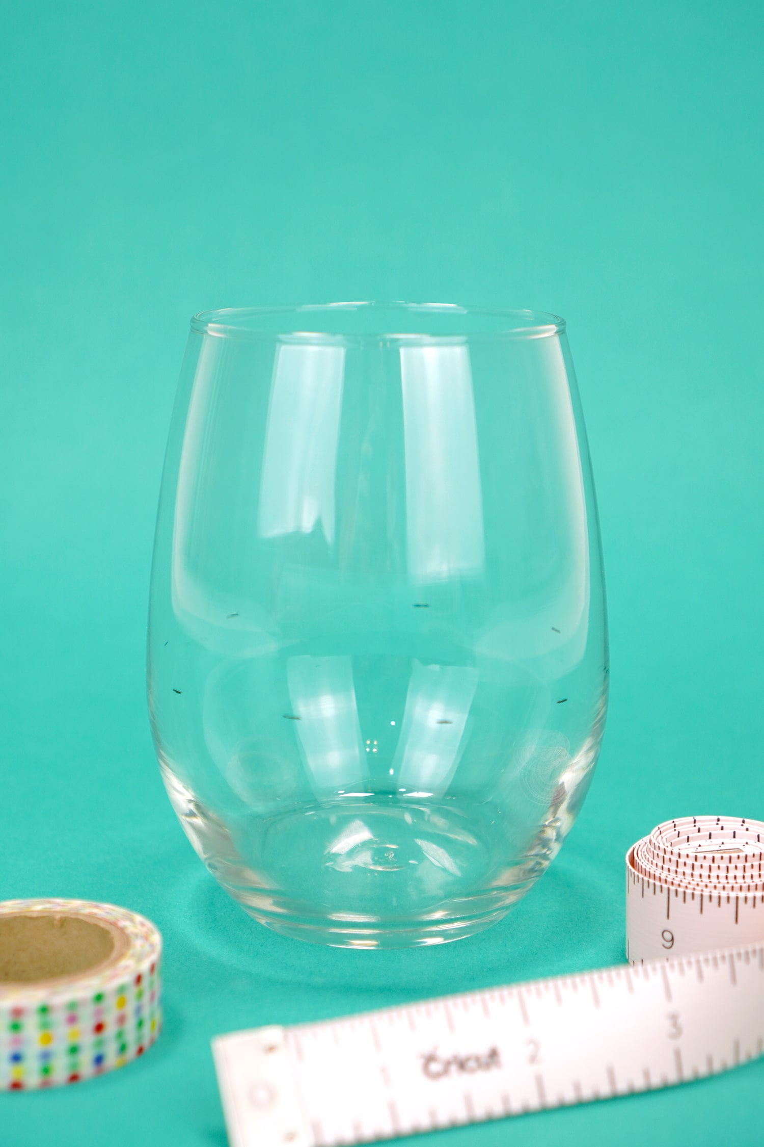 Clear stemless wine glass on teal background with washi tape and soft tape measure