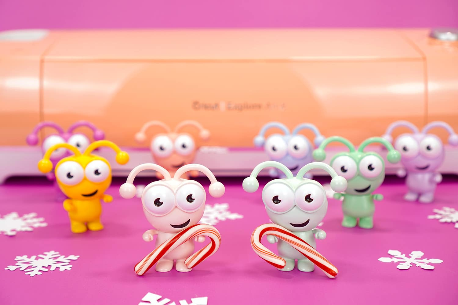 Rainbow colored Cricut Cutie figures holding candy canes on purple background with peach Cricut Explore Air 2 machine