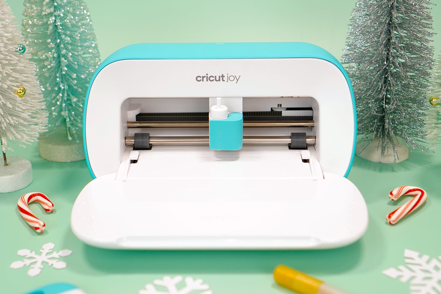 Cricut Joy machine with bottle brush trees, paper snowflakes, and candy canes on mint green background