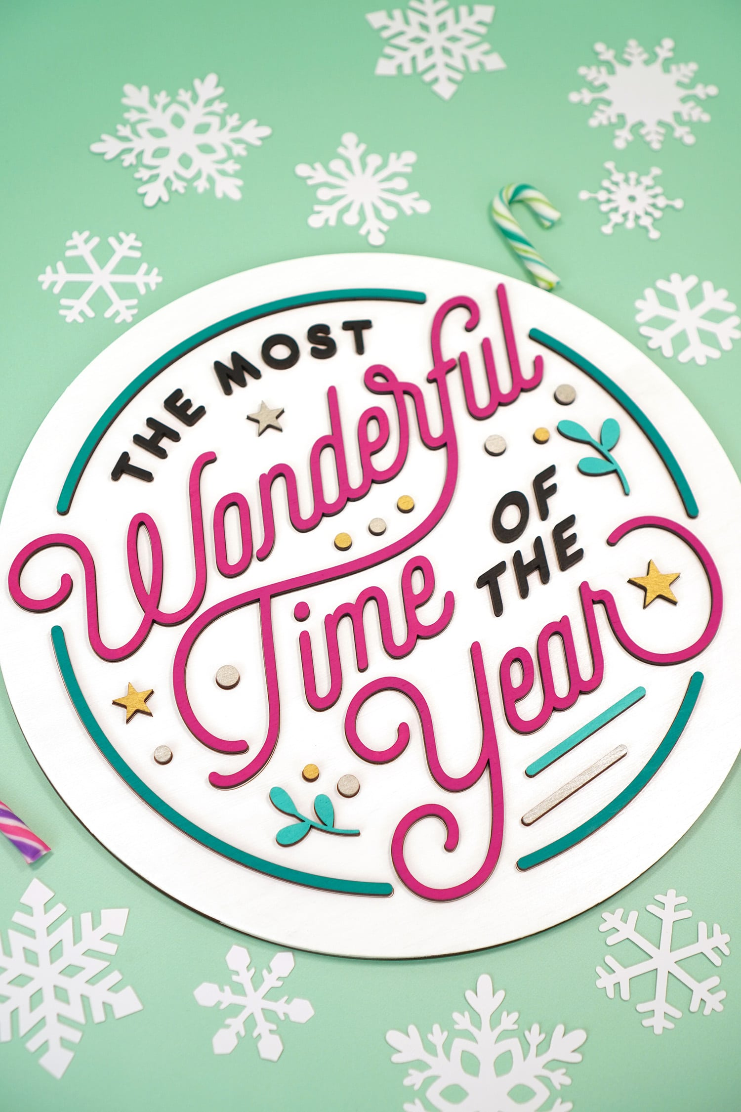 """""""The Most Wonderful Time of the Year"""" Laser Cut Wood Sign on mint green background with paper snowflakes and candy canes"""