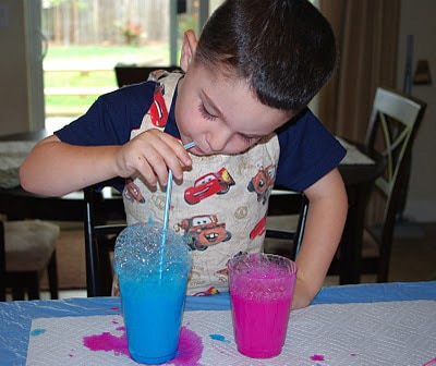 child blowing bubbles into cup of blue paint