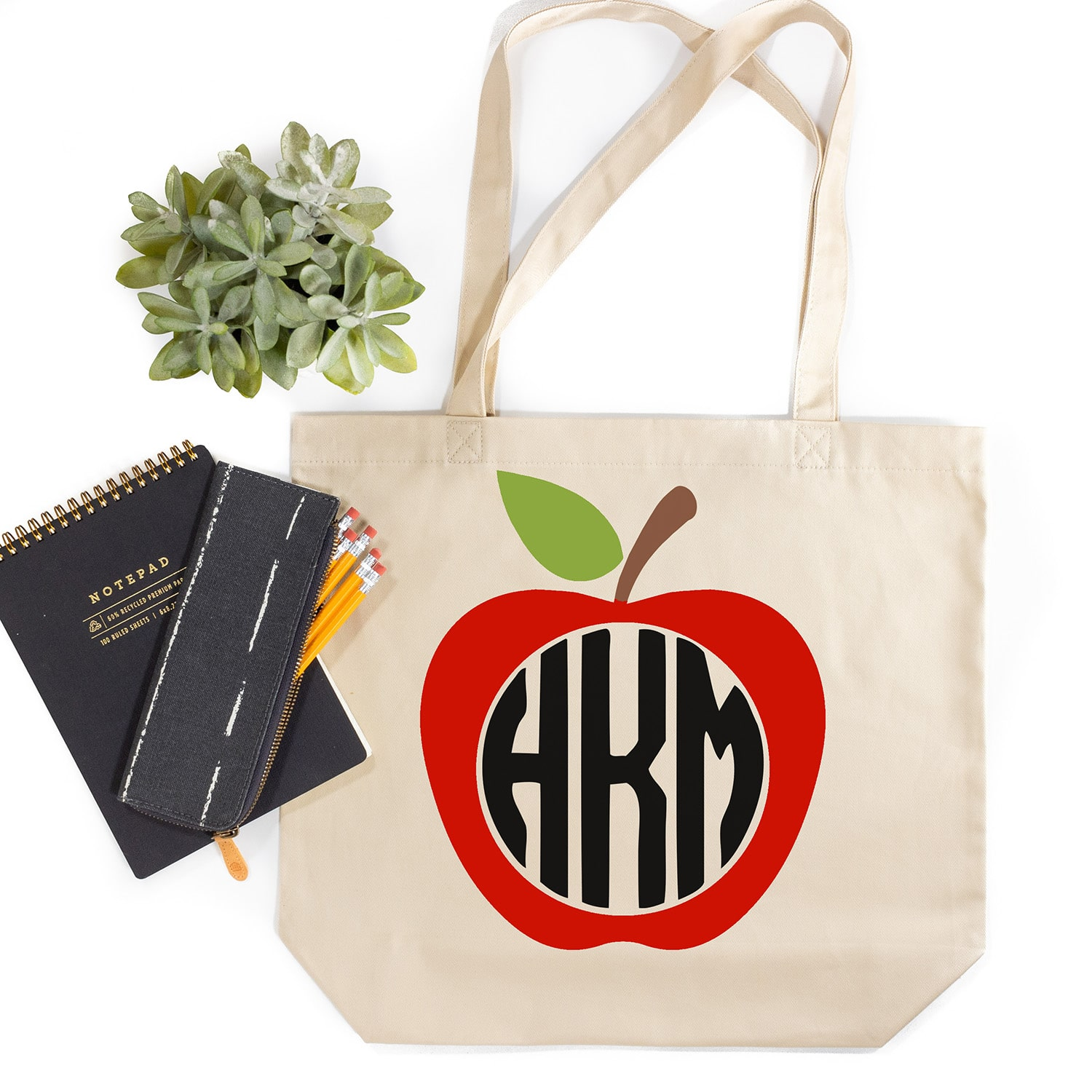 Tote bag with apple monogram design and notepad, pencils, and plant on white background