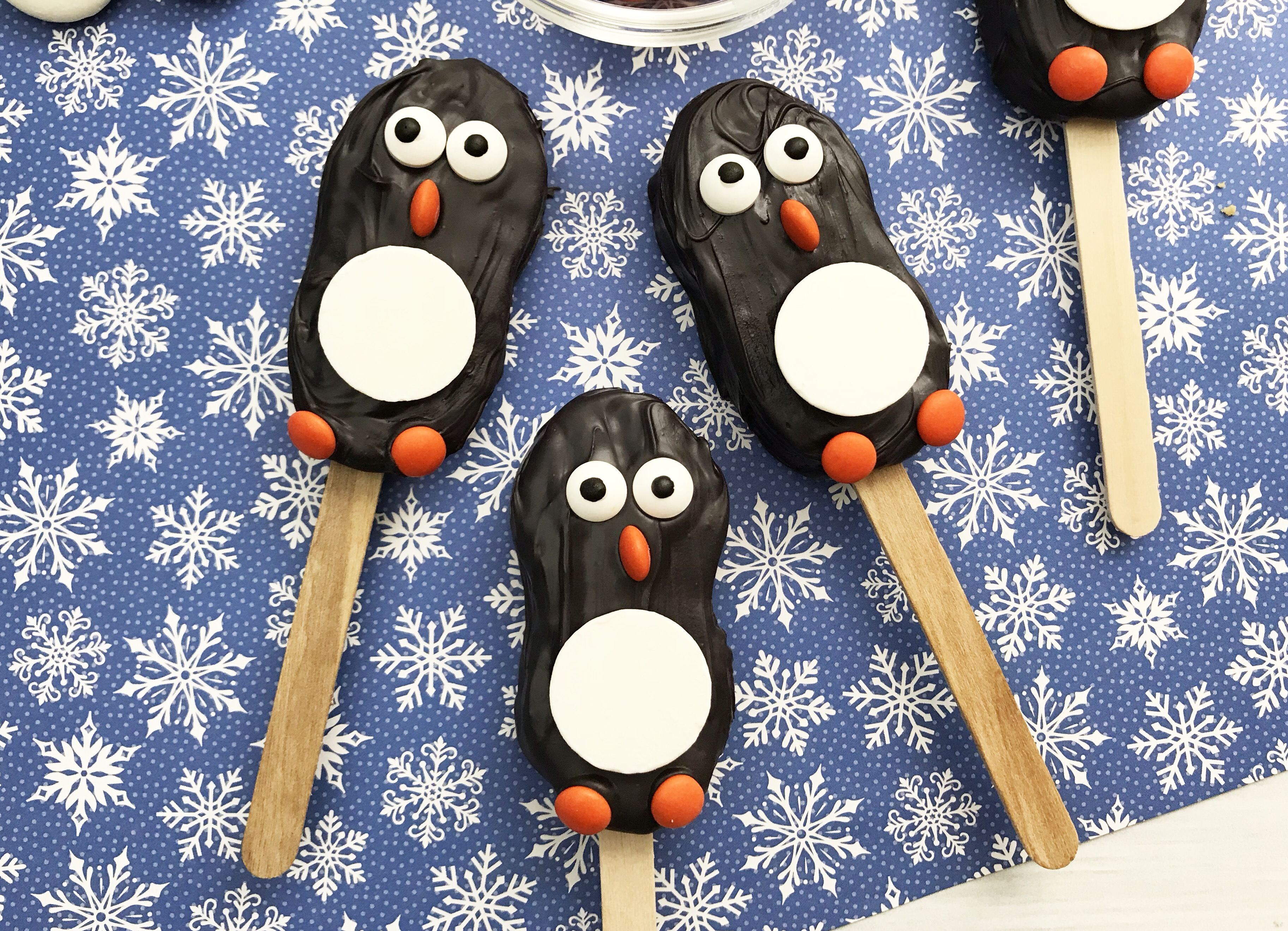 Penguin Nutter Butter Cookies on Blue Background with White Snowflakes