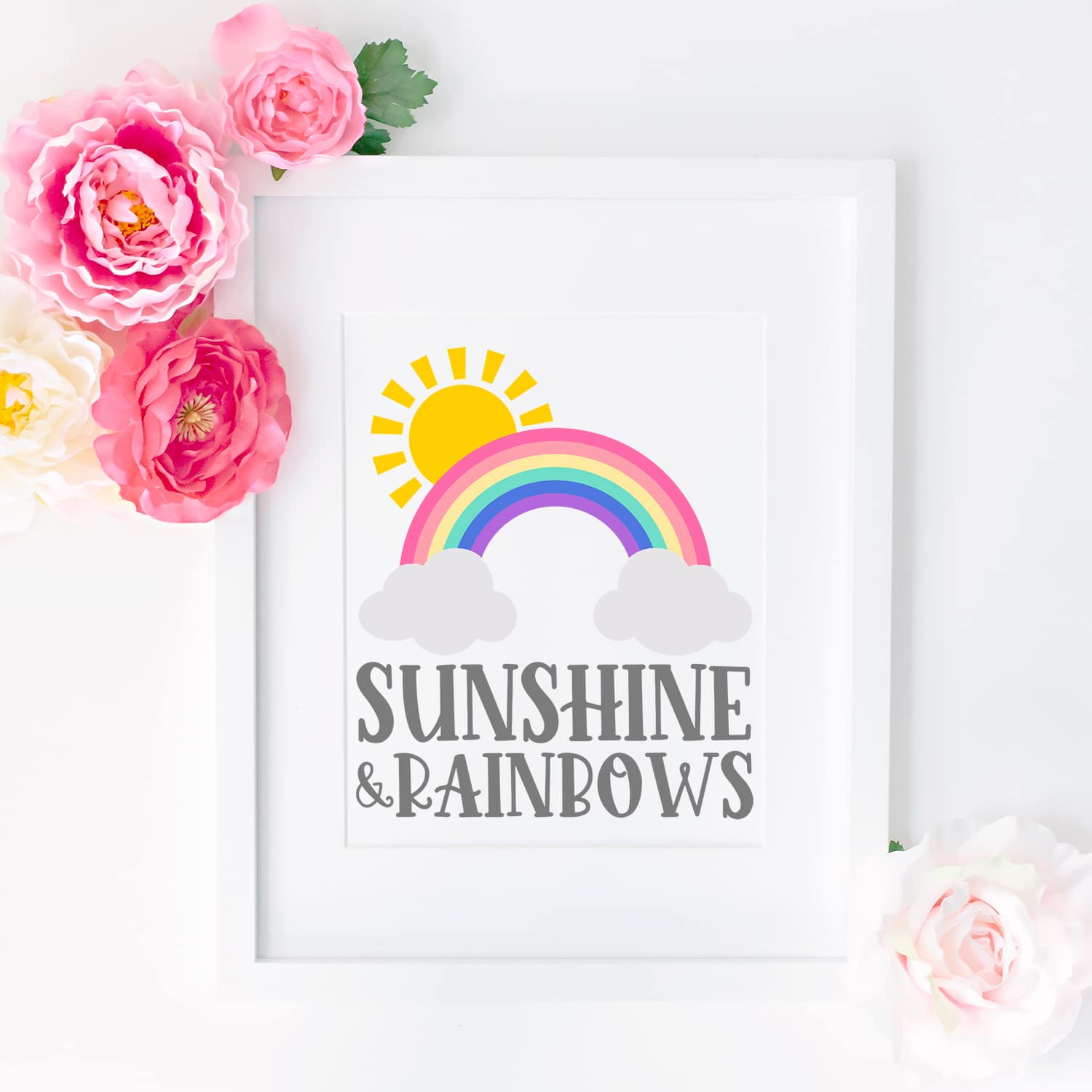 """Sunshine and Rainbows"" artwork in a white frame surrounded by pink and yellow flowers"